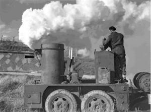 On comprend davantage le rôle et l'utilité du smoke generator lorsqu'on le voit fonctionner, comme ici. Source : Fonds du ministère de la Défense nationale, Belgium, 13 Oct. 1944, Bibliothèque et Archives Canada, numéro d'acquisition 1967-052 NPC, numéro de la pièce (créateur) : 41533, numéro de reproduction a167998-v6.