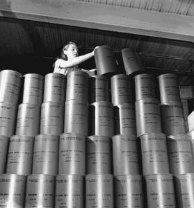 Cette photo permet de voir les contenants du Smoke Generator no 24, identiques à ceux produits à l'usine de munition de la Miner Rubber. Source : Fonds Office national du film du Canada, Division de la photographie, Montréal (Québec), mai 1944. Bibliothèque et Archives Canada, numéro d'acquisition 1971-271 NPC, numéro de la pièce (créateur) : WRM 4493, numéro de reproduction e-000762140.