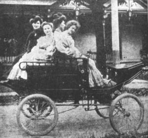 Cette photo, qui date de 1903, montre la première automobile de Granby, propriété de Simon Page. Prise devant la résidence de l'hôtelier, dans la rue Ottawa, on y voit Albina Page, assise à l'avant du véhicule, à la barre directionnelle, et Susie Mullin à ses côtés; Antoinette Page et Mlle Belisle occupent le siège arrière. Collection Société d'histoire de la Haute-Yamaska, P70-S27-SS05-SSS05-D1-P06