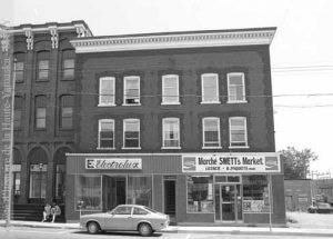 L'épicerie boucherie Swett Bros. est un client régulier de Pine Tree Farm. Le commerce de la rue Principale s'y procure une grande quantité de viandes de mouton et d'agneau, destinées à la population anglaise de la ville. L'édifice, tel qu'il apparaît en 1978. (Fonds Patrimoine architectural, inventaire et analyse, SHHY)