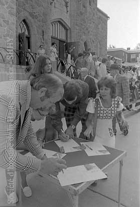 À la sortie de l'église Saint-Eugène, des citoyens signent la pétition du Comité pour la conservation de la bibliothèque. (©SHHY, fonds Jeannot Petit, P026-19730805-D001-P005)