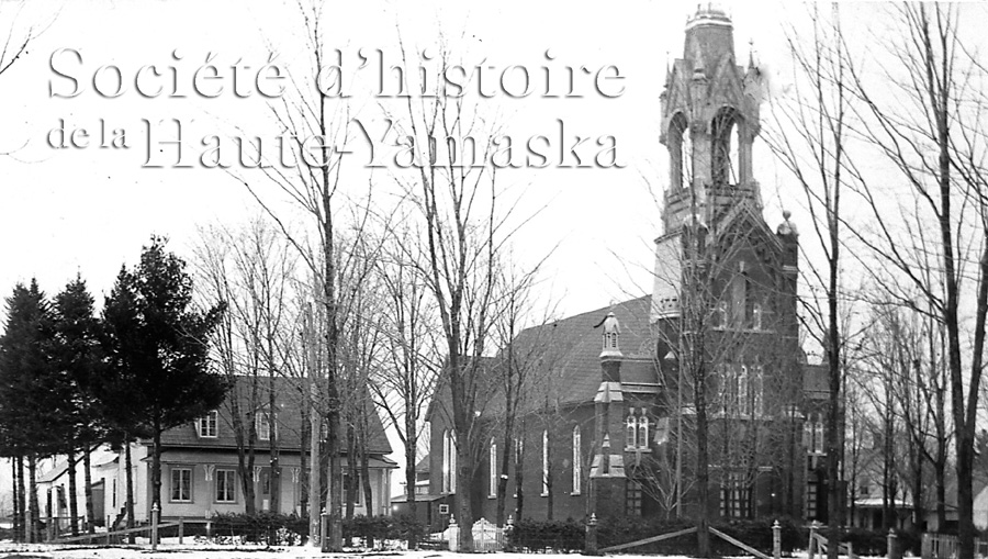 Le presbytère et l'église de la paroisse catholique Sainte-Pudentenne, vers 1910. (© Coll. Société d'histoire de la Haute-Yamaska, P070-H017-B1-P001)